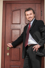 realtor opening wooden door and smiling