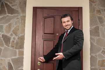 realtor opening wooden door and smiling welcoming.