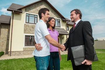 Salesman shaking hands with property owners.