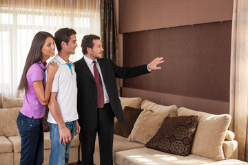 man real estate agent showing couple new house.