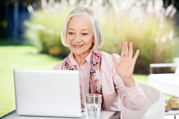 Senior Woman Waving While Video Chatting On Laptop