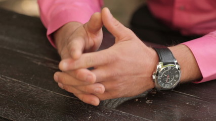 Closeup of man's hands with the clock on the table