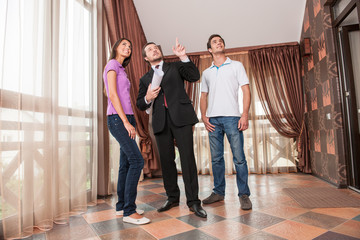 man real estate agent pointing to ceiling of new house.
