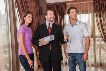 waist up of male real estate agent smiling with two clients.