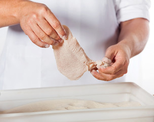 Butcher Adding Flour To Chicken Meat