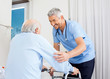 Caretaker Helping Senior Man To Use Walking Frame - 72607756