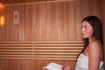 Caucasian young woman enjoying sauna.