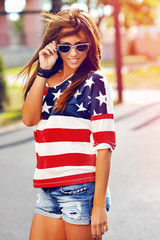 Fashion portrait of young hipster woman wearing sunglasses at su