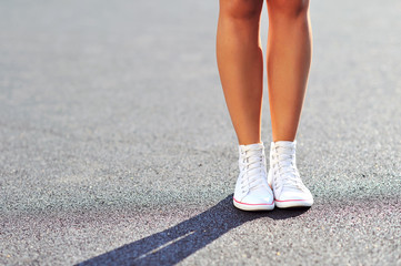 Woman legs in sneakers