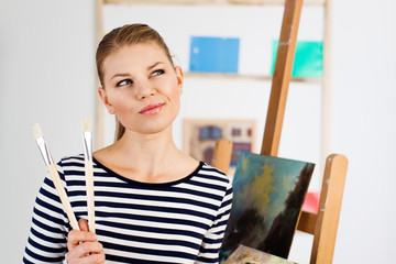 Portrait of thinking woman professional painter holding brushes