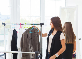 Portrait of attractive teen girl making choices clothes