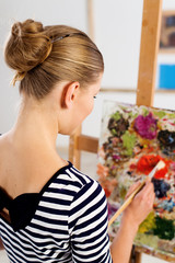 Female art student working over picture at easel in university