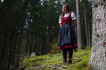 woman in traditional clothes walking in a forest.