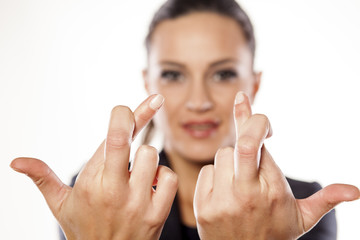 Beautiful business woman showing crossed fingers for a luck
