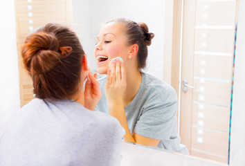 Beauty girl cleaning her face with cotton pad at home