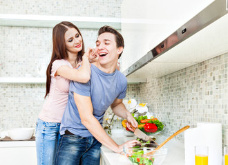 Husband and wife preparing food in the kitchen