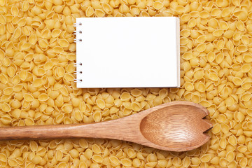 wooden spoon on uncooked macaroni and notebook