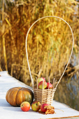 Pumpkin and basket with apples on table