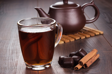 cup of tea with cinnamon sticks and teapot