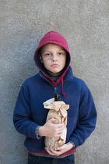 homeless boy holding a bottle alcohol