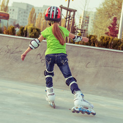 Back view of little girl in helmet on roller-skates in park
