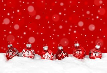Rote Weihnachtskugeln im Schnee