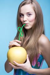 beautiful girl drinking pomelo juice through a straw