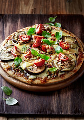 Aubergine and tomato pizza with basil leaves