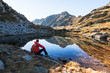 Male hiker takes a rest sitting next a mountain lake
