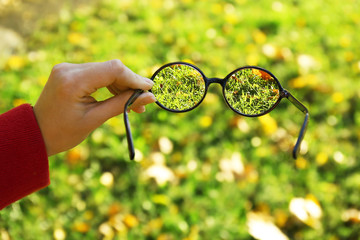 Vision concept. Glasses in hand on green grass background