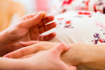 Hebamme gibt Schwangeren Akupunktur
