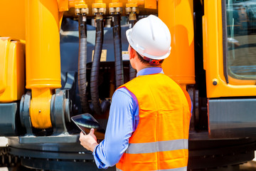 Engineer checking motor of construction machine