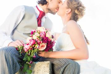 Hochzeitspaar küsst auf Feld in Liebe