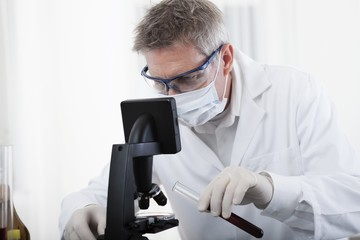 doctor looking on microscope and analyse blood
