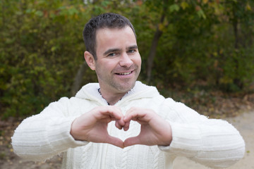 man outside shaping heart with his hands