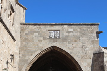 arms above the arched entrance