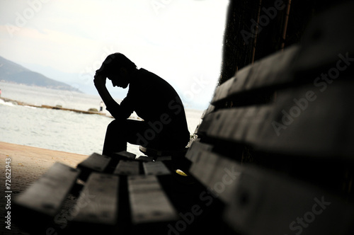 depressed young man sitting on the bench - 72622943