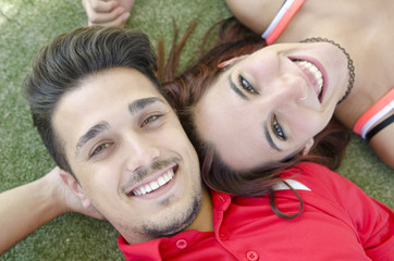 Couple on grass smiling and looking at camera