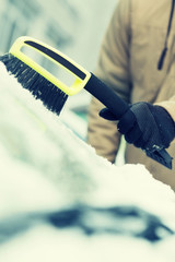 man cleaning snow from car windshield with brush