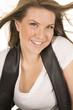 woman white shirt black vest close hair blow smile