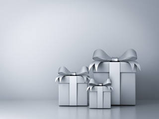 Gift boxes with silver ribbon bow and empty white wall