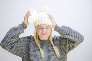 Girl in winter clothes having headache banging cup of her head