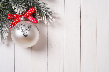 Christmas fir tree and bauble with red ribbon on wooden board wi