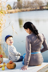 Little boy with her mother on the autumn lake
