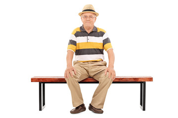Casual senior gentleman sitting on a wooden bench