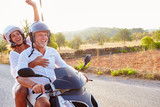 Mature Couple Riding Motor Scooter Along Country Road