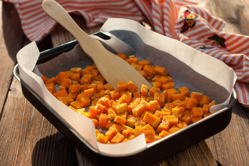 pumpkin with salt, spices and olive oil in a pan for baking