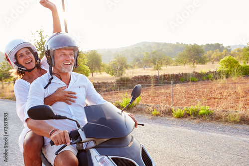 Mature Couple Riding Motor Scooter Along Country Road - 72631983
