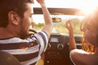 Young Couple Driving Along Country Road In Open Top Car