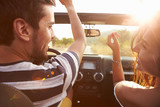 Young Couple Driving Along Country Road In Open Top Car poster